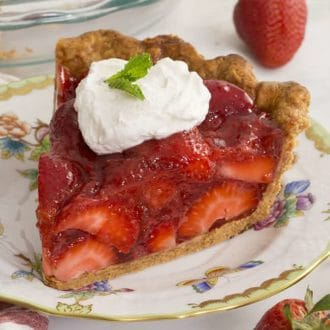 A piece of strawberry pie topped with a dollop of whipped cream