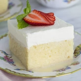 A piece of tres leches cake topped with a fan of strawberry slices