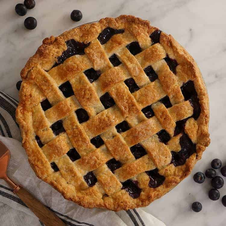 A top down shot of a blueberry cake with a lattice top