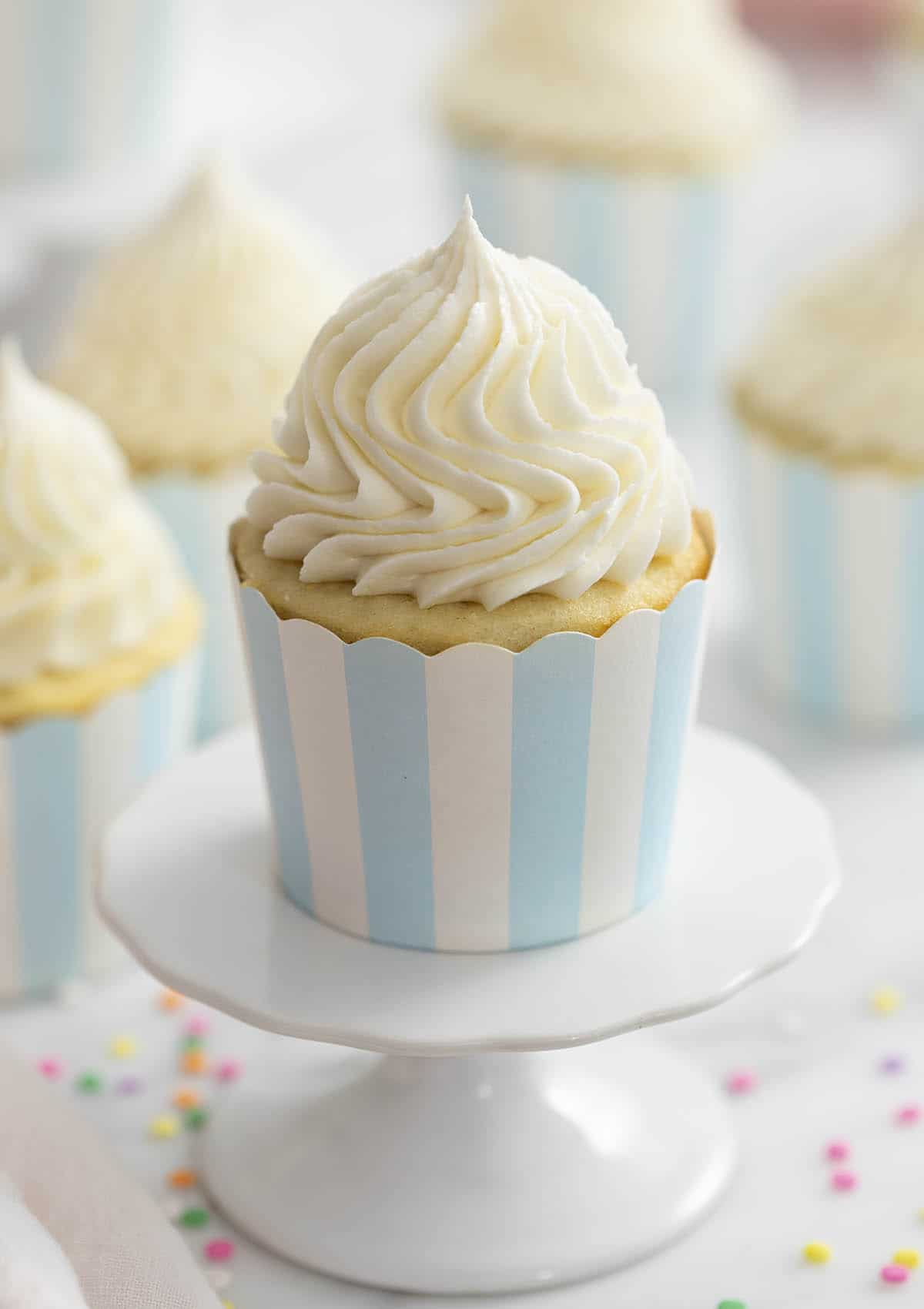 A photo of a vanilla cupcake on a cupcake stand with vanilla buttercream frosting beautifully piped on top.