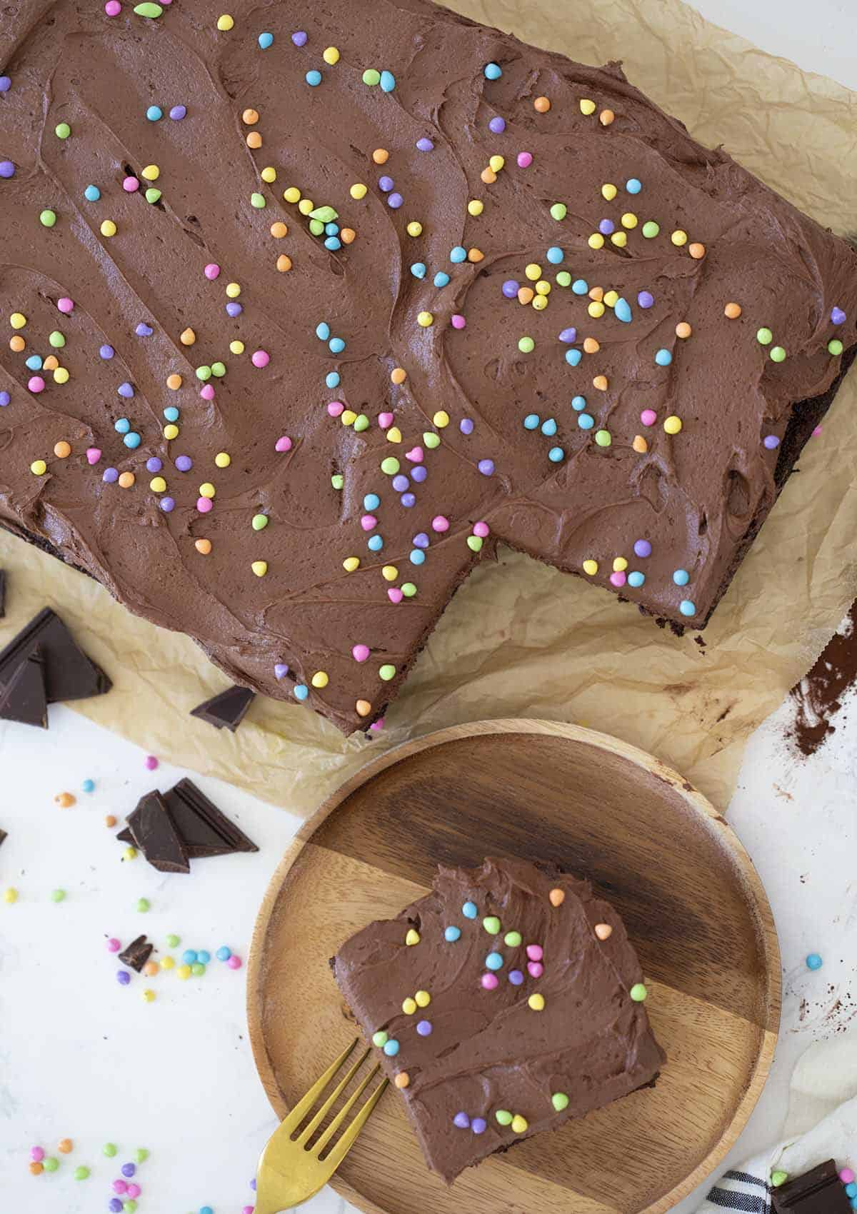 A top down shot of a chocolate sheet cake topped with sprinkles.