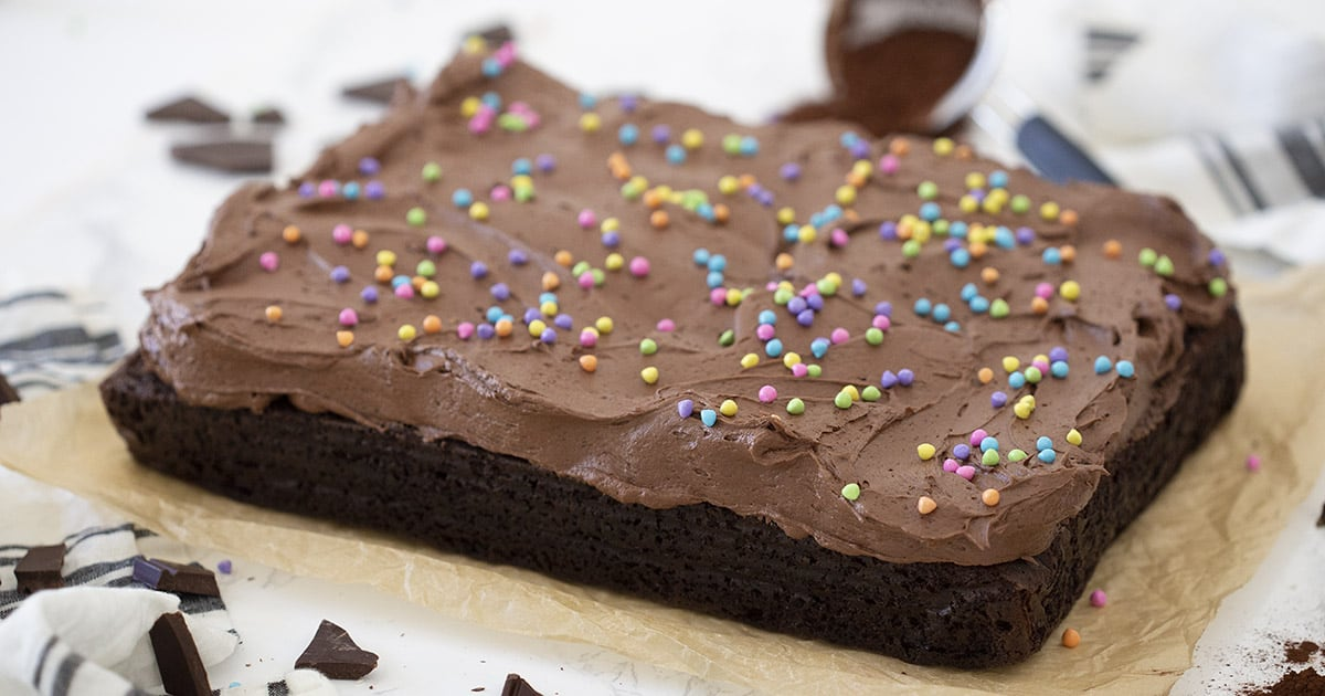 A delicious chocolate sheet cake on a piece of parchment paper.