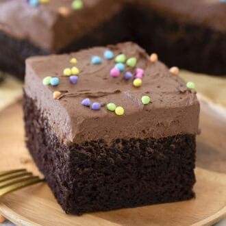 A piece of chocolate sheet cake on a wooden plate.