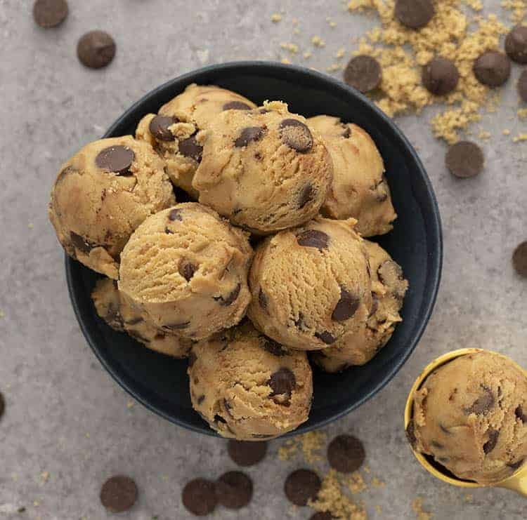 Scoops of cookie dough in a navy bowl.