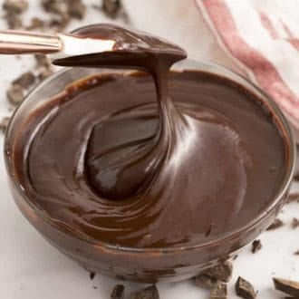 a bowl of chocolate ganache being swirled with a spatula