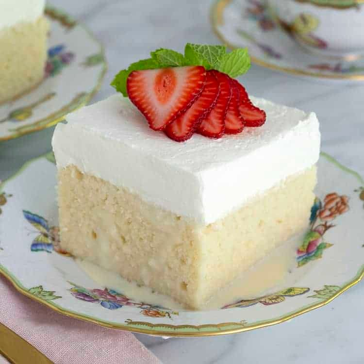 A piece of tres leches cake topped with whipped cream and strawberries.