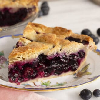 A slice od delicious Blueberry Pie on a porcelain plate.
