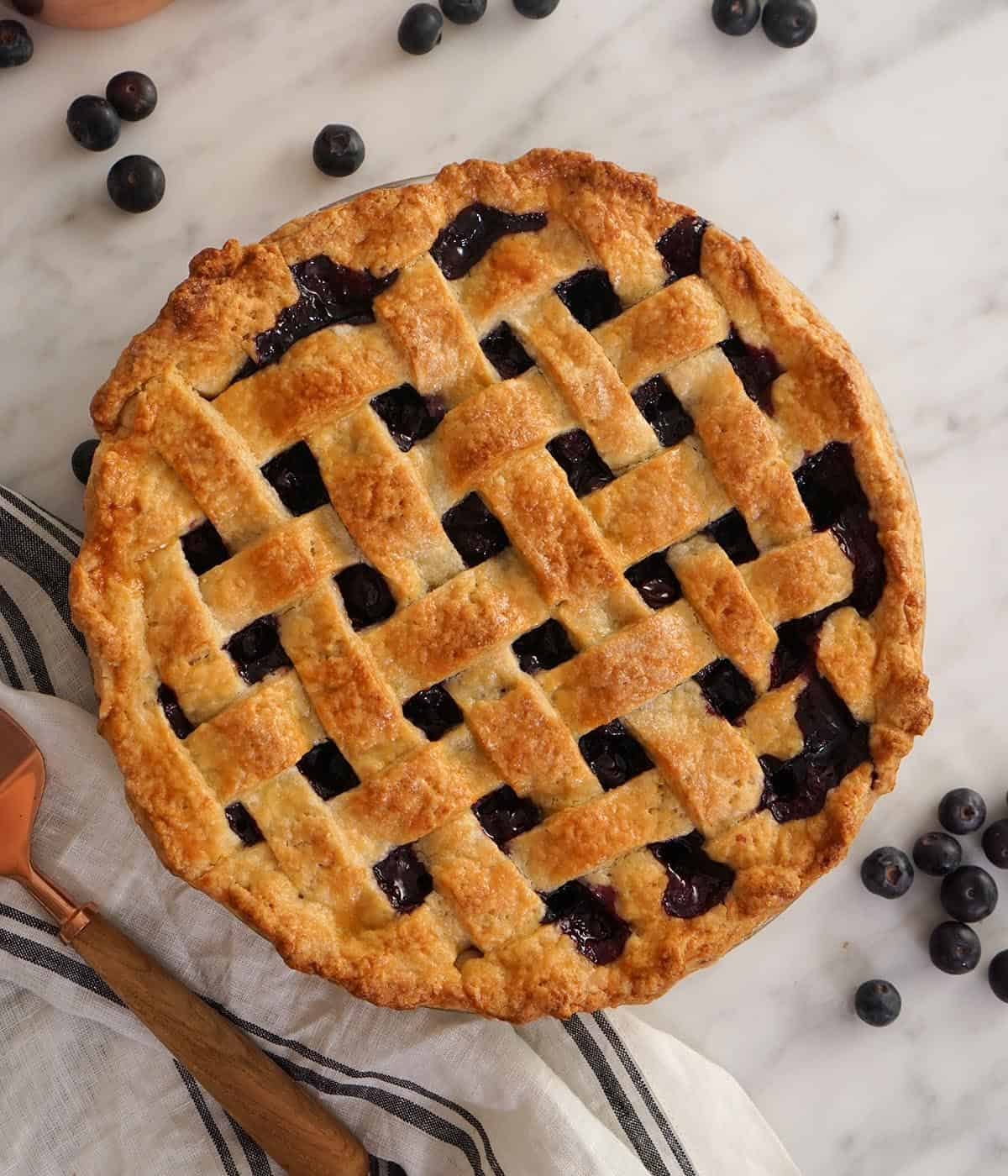A top-down view of a blueberry pie with a lattice top.
