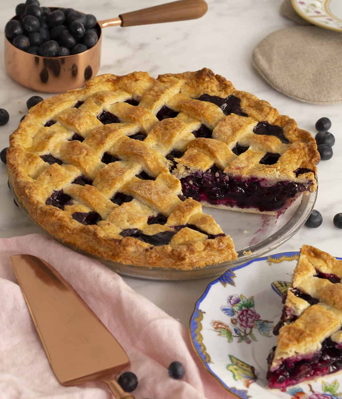 A homemade blueberry pie on a marble table.