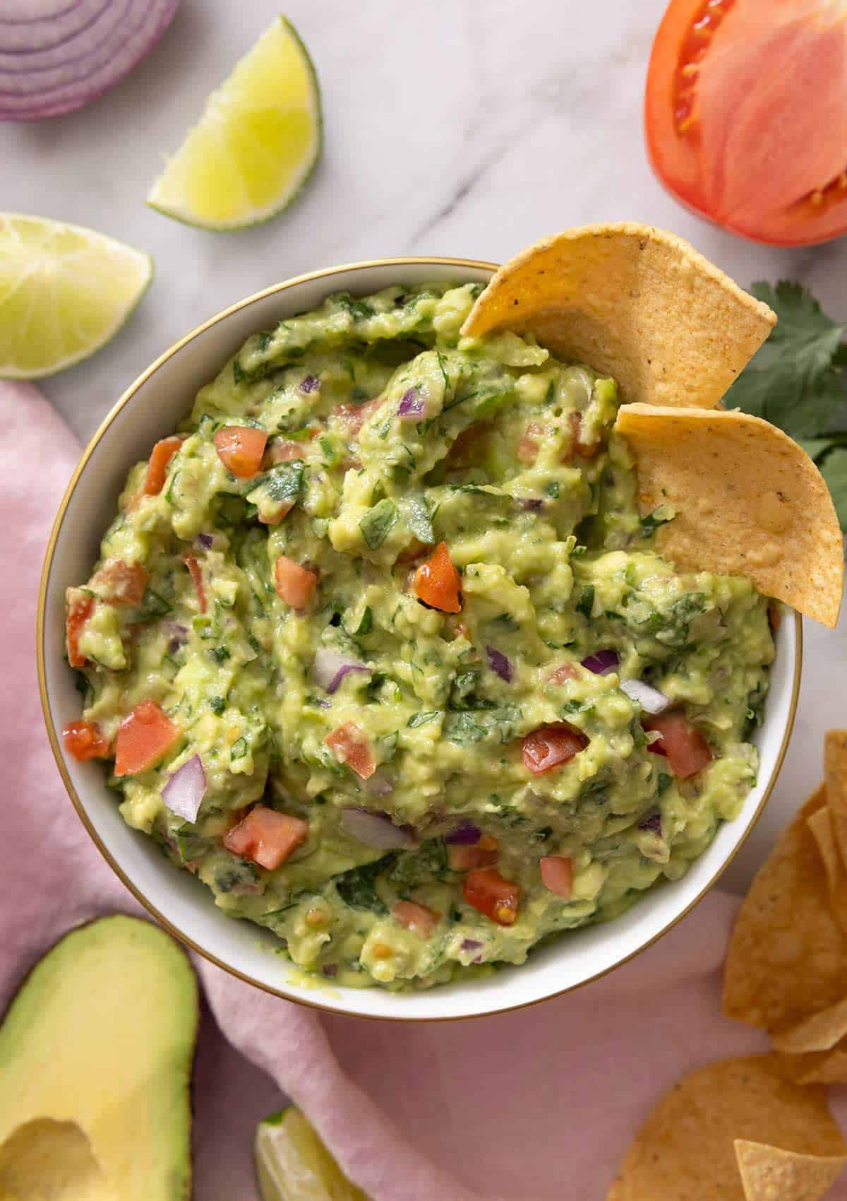 An overhead shot of a bowl of guacamole with tortilla chips at the side