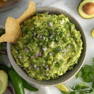 guacamole in a white bowl with chips on the side