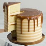 A salted caramel cake with stripes and a caramel drip on top