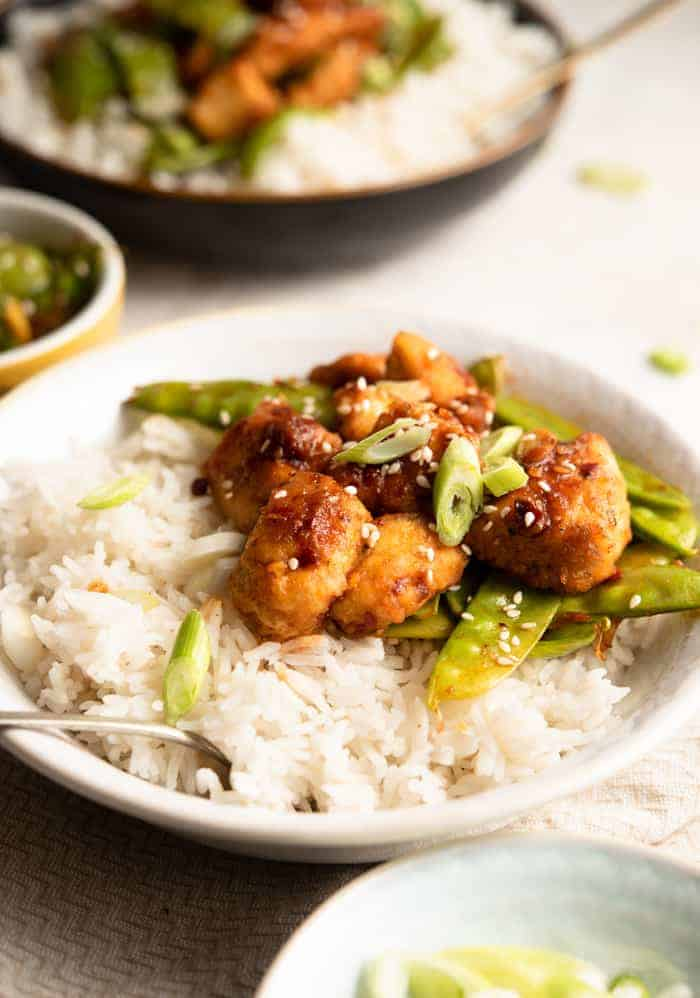 A side shot of crispy Szechuan chicken in a bowl with rice