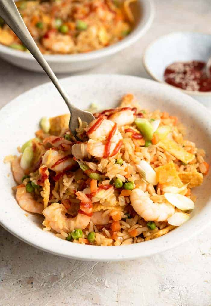 A side shot of shrimp fried rice in a bowl topped with sriracha sauce