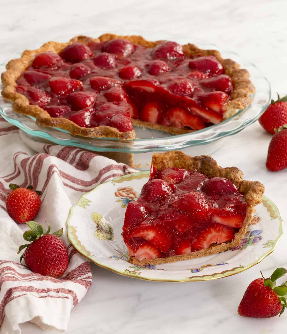 A fresh strawberry pie with a piece in the foreground on a white marble table.