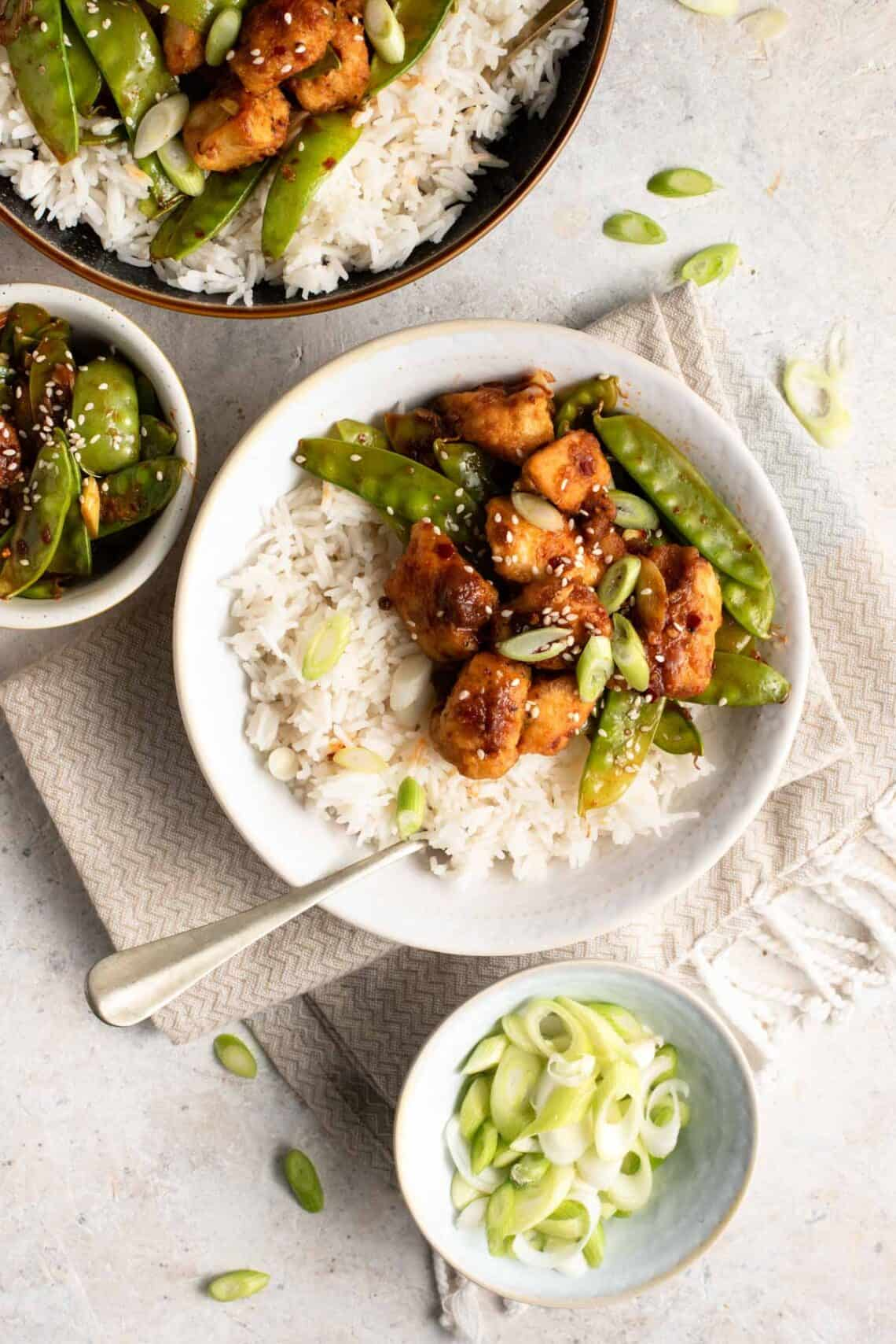 An overhead shot of Szechuan chicken in a bowl with rice and snow peas