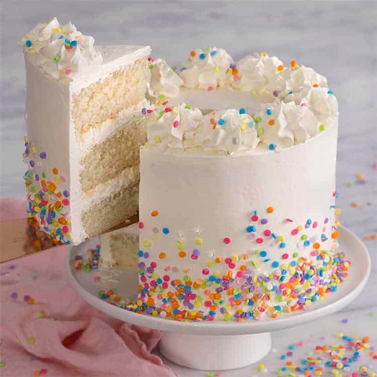 A three layer white cake covered in sprinkles