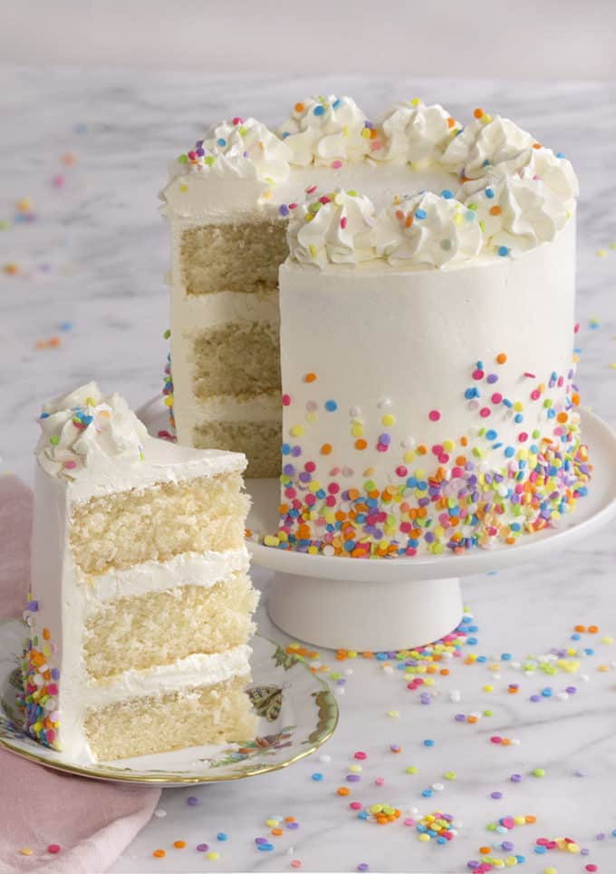 A white cake on a cake stand with a piece out in the foreground