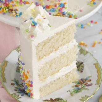 A piece of three layer white cake with white frosting and sprinkles on a plate.