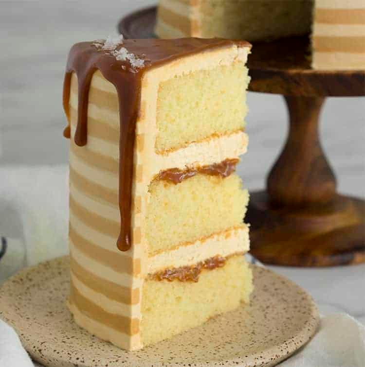 A piece of three layer salted caramel cake on a small plate