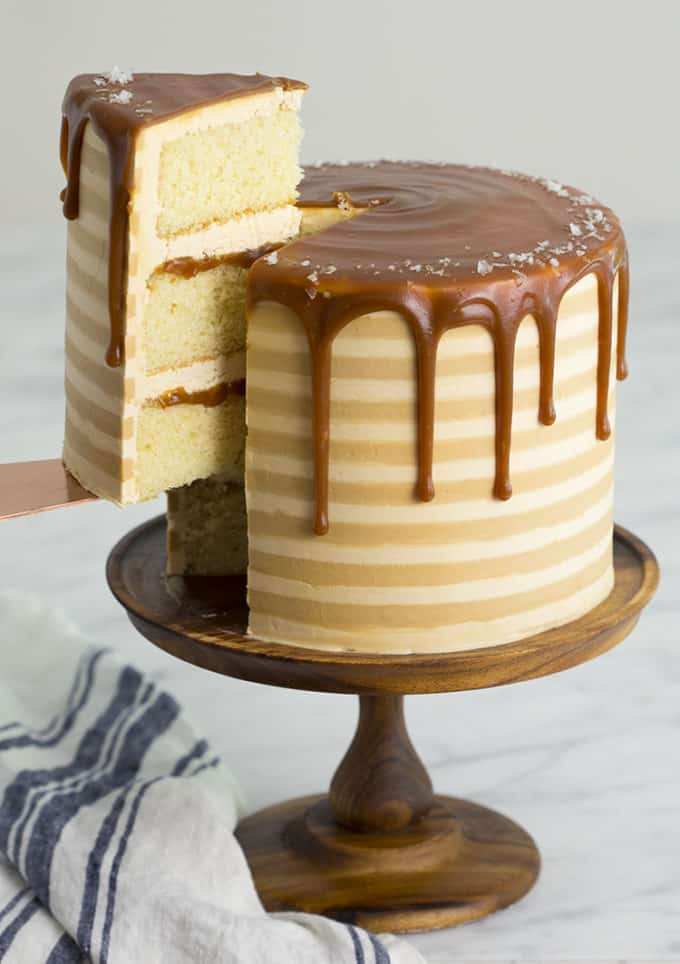 A striped salted caramel cake on a wooden cake stand
