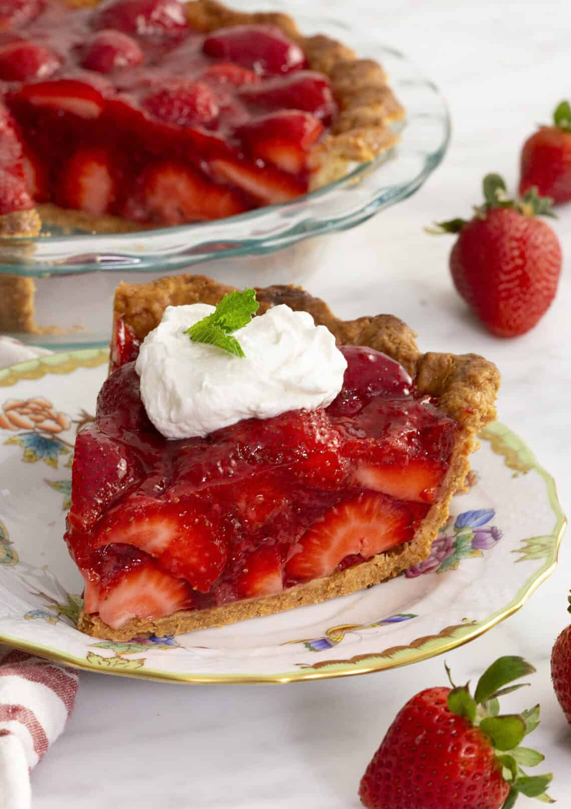 A piece of strawberry pie on a porcelain plate.