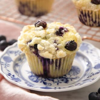 A delicious blueberry muffin with a crumble topping on a blue and white plate.