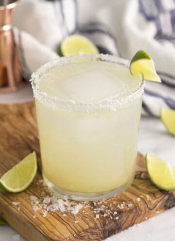A scratch margarita in a tumbler garnished with a lime wedge.