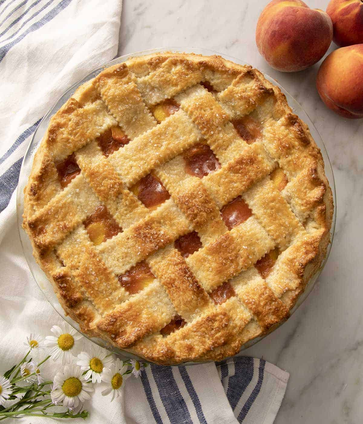 A peach pie with a pastry lattice on a marble counter.