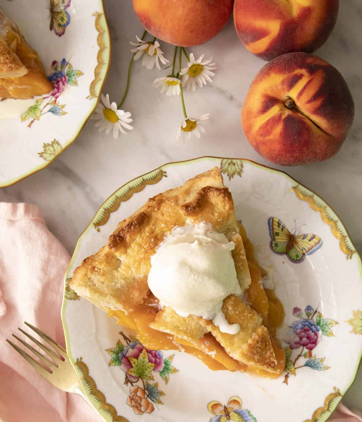 A top-down photo of a peach pie piece with melting vanilla ice cream on top.