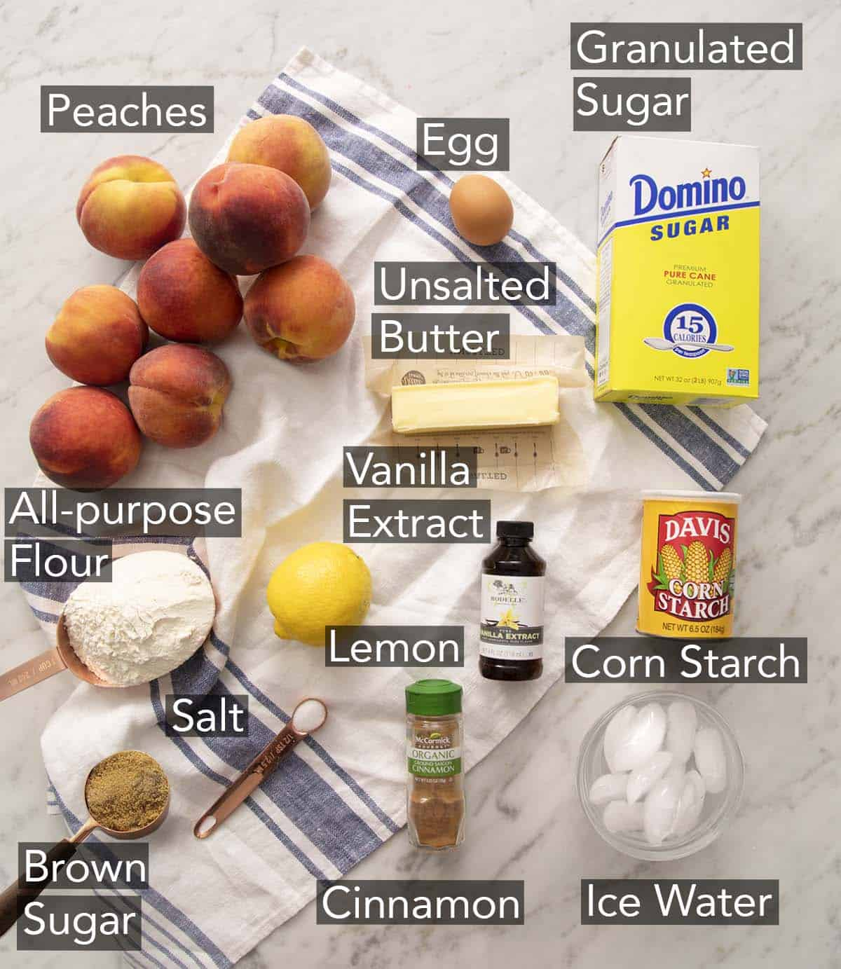 Ingredients to make peach pie on a marble counter.