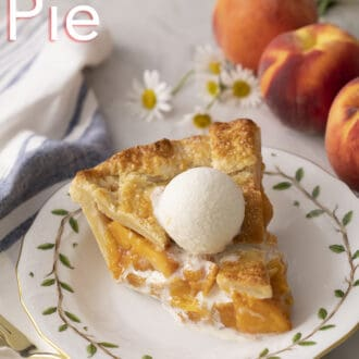 A piece of peach pie next to some flowers and peaches.