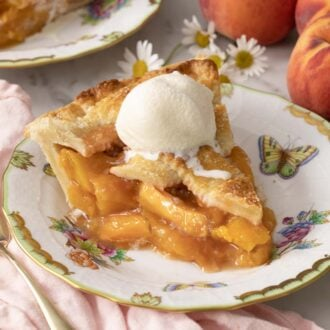 A piece of peach pie with a scoop of vanilla ice cream on top.