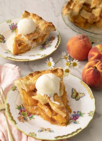 Two pieces of peach pie on porcelain plates with ice cream.