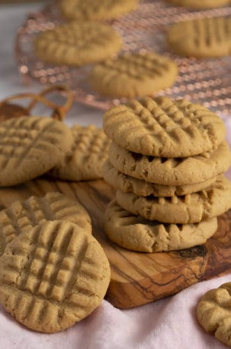 A stack of peanut ubtter cookies on a small wooden board