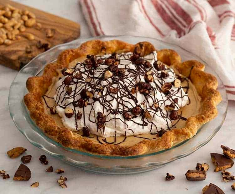 A chocolate peanut butter pie with whipped cream and chocolate covered peanuts