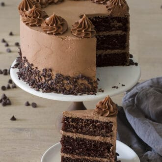A three layer chocolate cake topped with buttercream dollops on a cake stand.