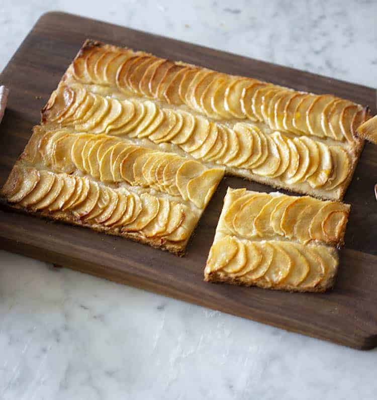 An apple tart on a wooden cutting board with a piece removed.