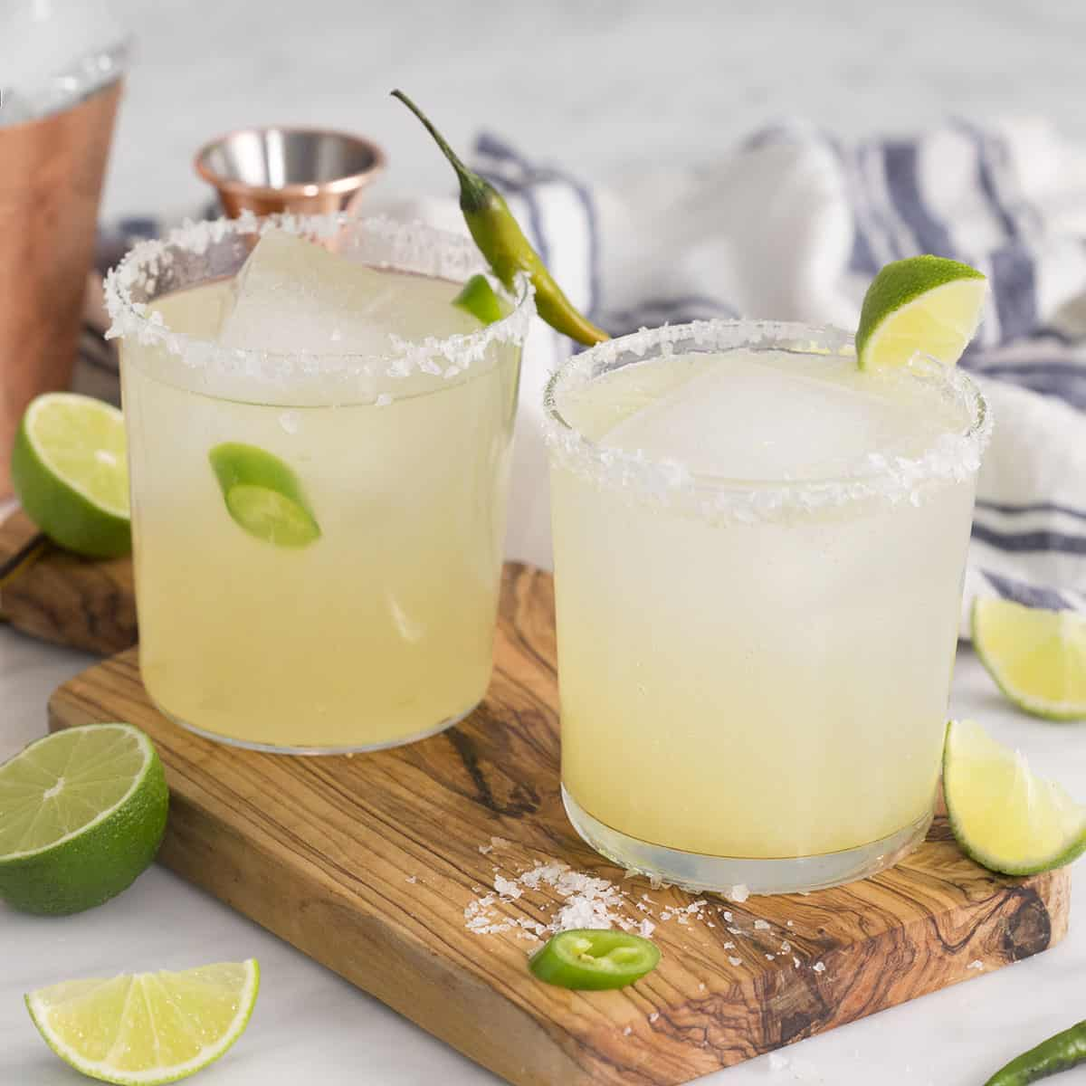 two margarita cocktails on the rocks with salt in a tumbler