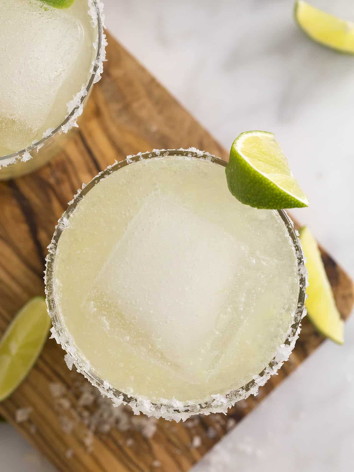 A top-down view of a margarita on a wooden cutting board