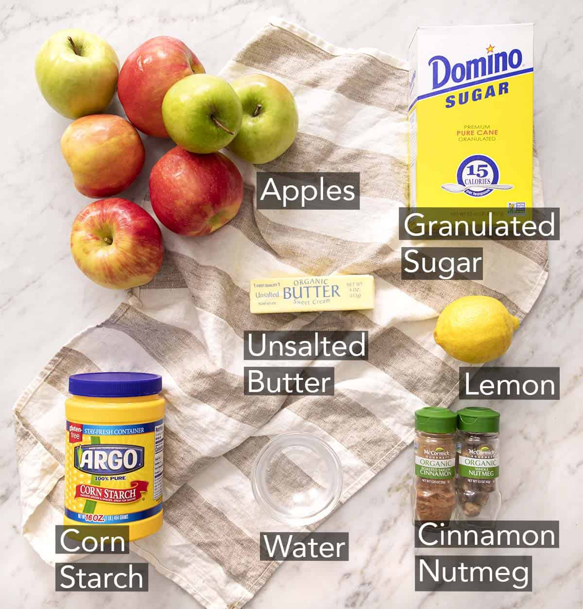 Ingredients to make apple pie filling on a marble counter.