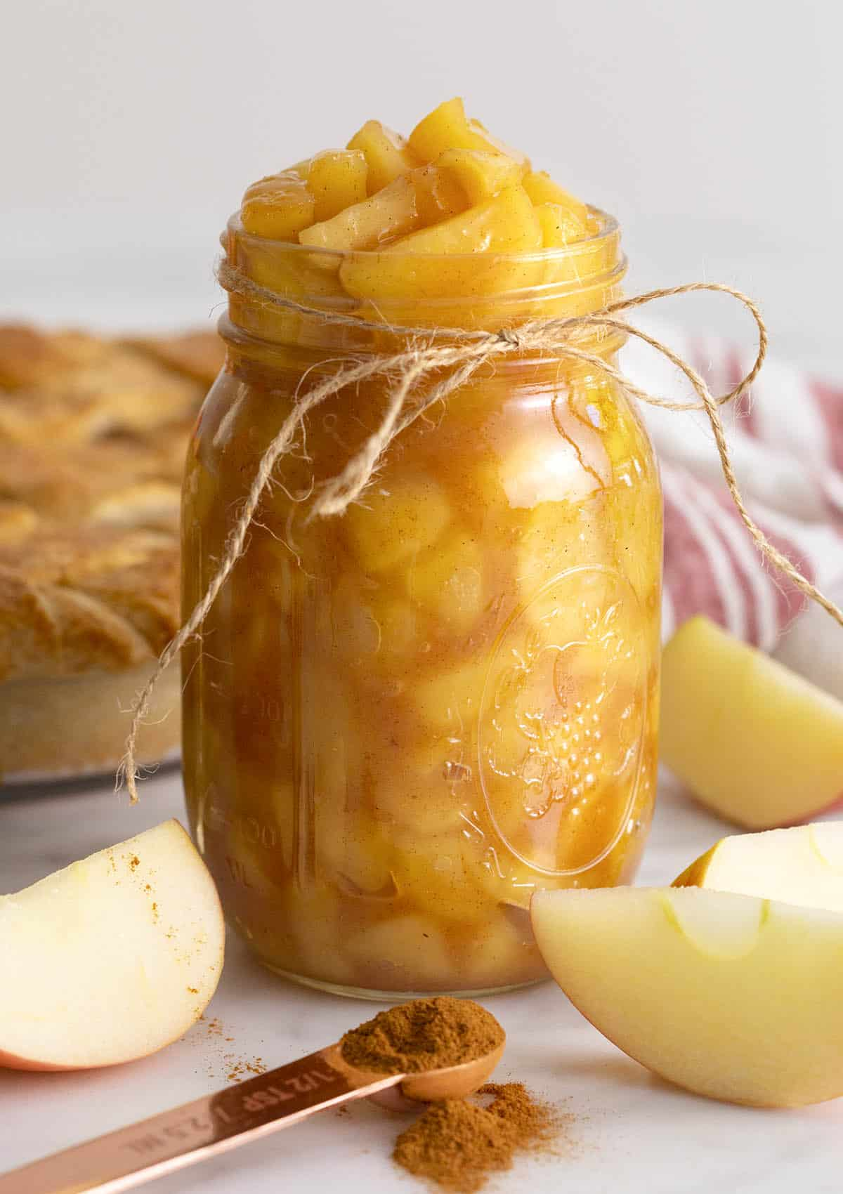 A big jar of apple pie filling next to some apple slices.