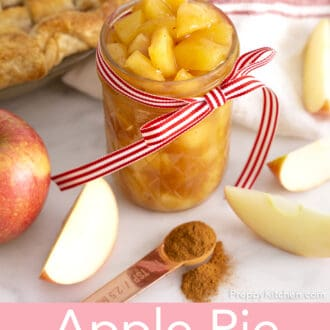 Apple pie filling in a mason jar tied with a red and white ribbon.