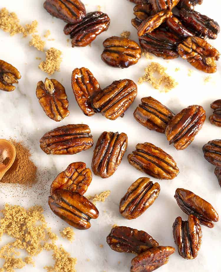 A group of candied pecans on a white marble table with cinnamon and brown sugar in frame