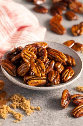A plate of candied pecans next to some brown sugar.