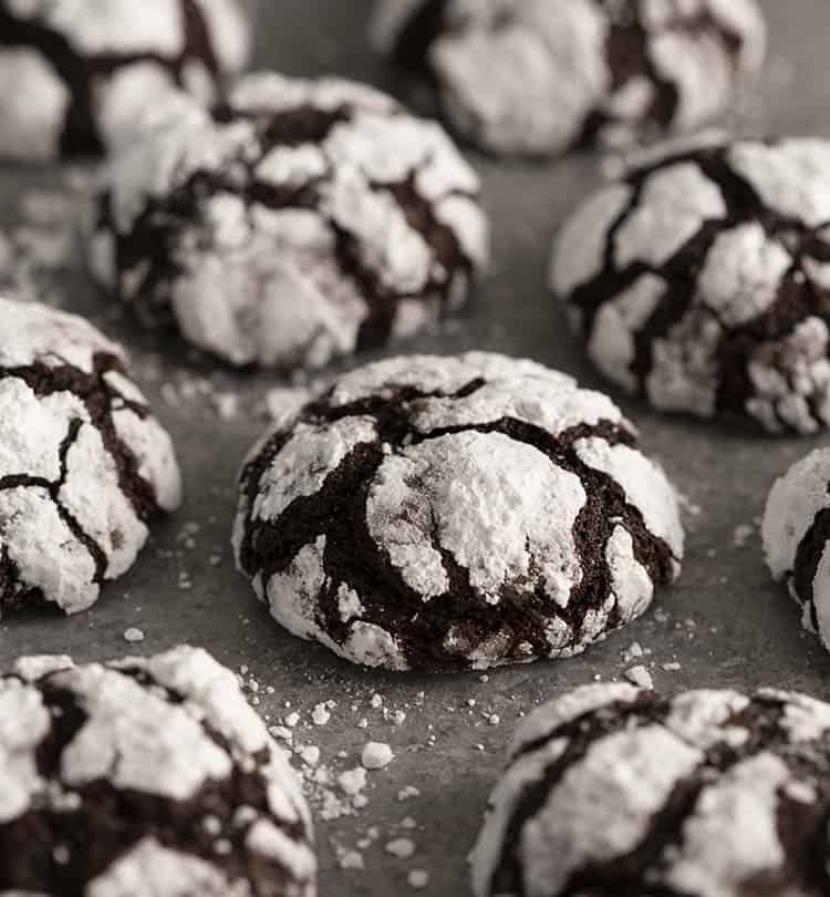 Chocolate crinkle cookies on a grey surface scattered with powdered sugar.