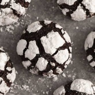 A chocolate crinkle cookie on a grey surface with powdered sugar around it.