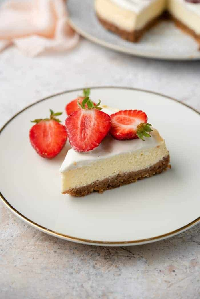 A slice of instant pot cheesecake on a plate with strawberries on top