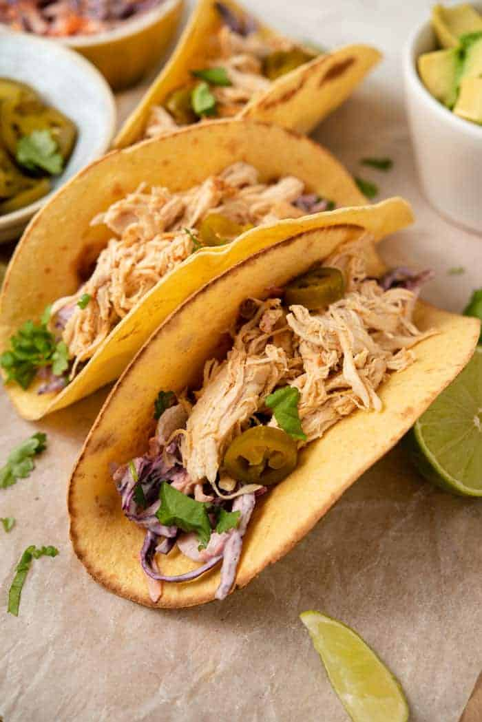 A close up of instant pot chicken tacos in a corn tortilla