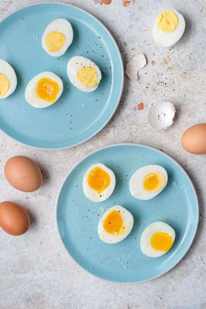 An overhead shot of hard boiled eggs and soft boiled eggs on two blue plates